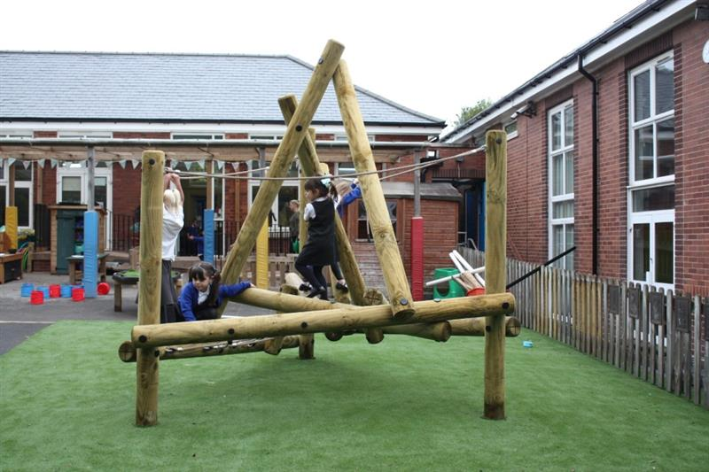 Children climbing on a log and rope climbing frame