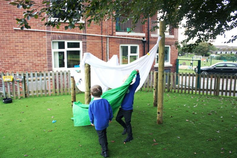Children using material to build a den using den making posts