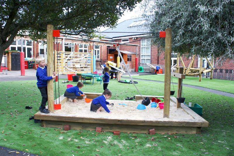 Children playing in a huge sand pit in the school playground