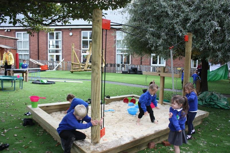 Children digging in a sand pit in the school playground