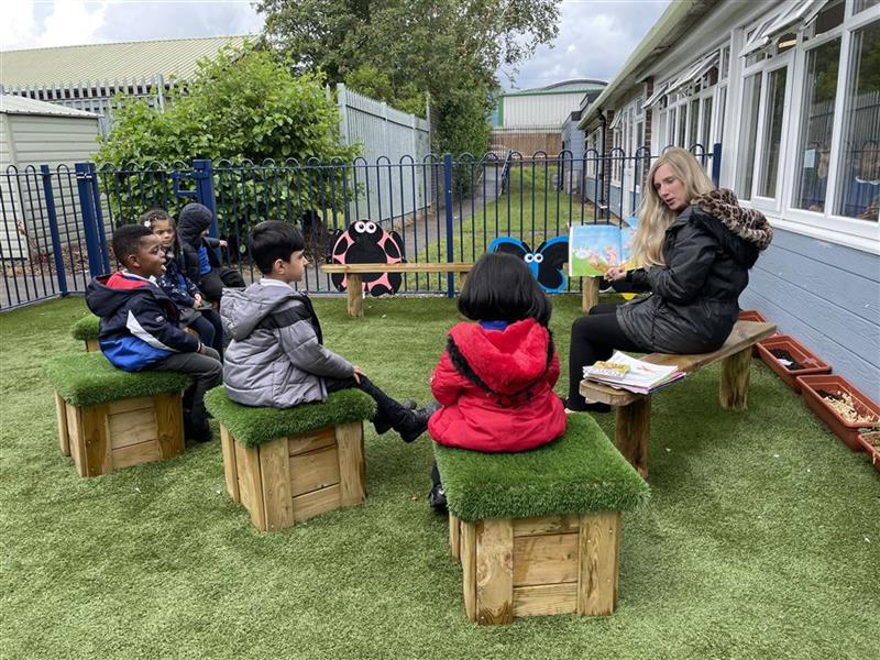 Four children in coats sat on grass top seats with a teacher reading a book to them.