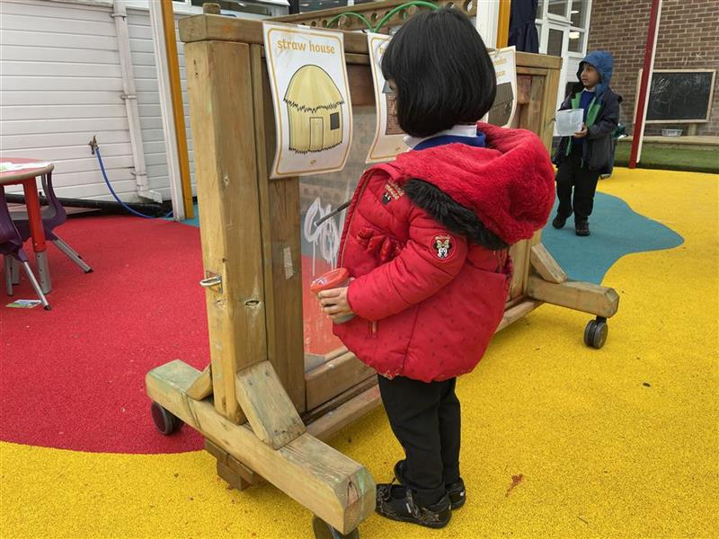 A young girl painting on our moveable paint panel, one young boy is walking behind her holding a picture.