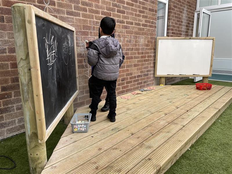 A young boy playing on our performance stage with another child, they are drawing on the giant chalk boards on the stage.