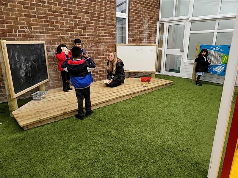 Three children playing on our performance stage which includes a chalkboard with a teacher accompanying them.