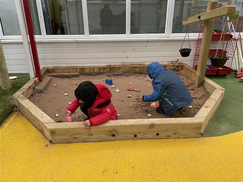 Two children playing inside a sand box, they are using spades to dig in the sand.