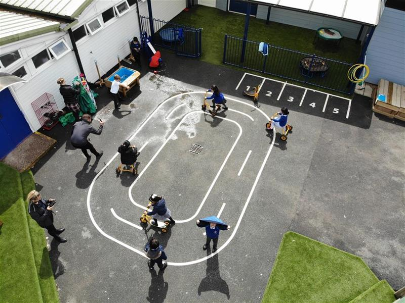 A birds eye view of 5 children playing on the roadway using bikes, trikes and scooters. 1 young boy is playing in the water box whilst 2 adults are accompanying the children.