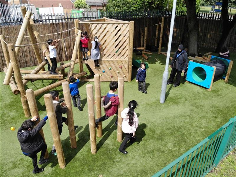 9 children playing on and around our Harterfell Climber and Climbing Poles, 1 teacher is accompanying them.