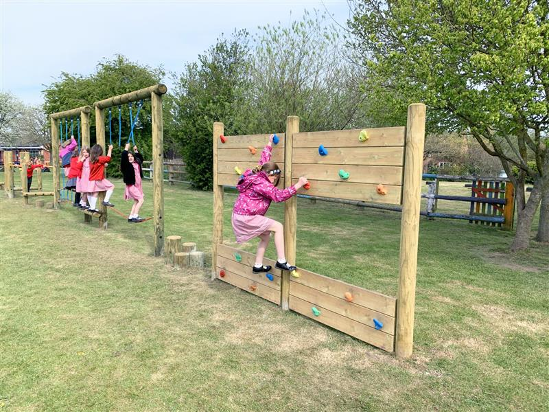 4 children moving across a selection of trim trail challenges including a climbing wall, tightrope traverse and stepping logs