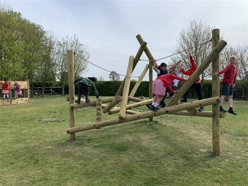 3 children balancing on the beams of a bowfell climber installed onto natural grass