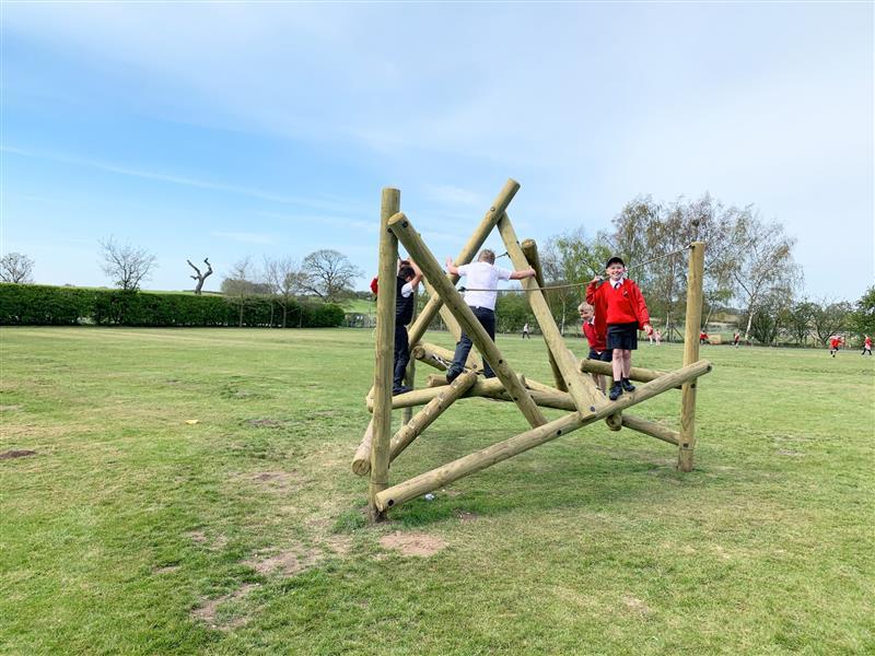 4 children climbing on a bowfell climbing frame installed into natural grass