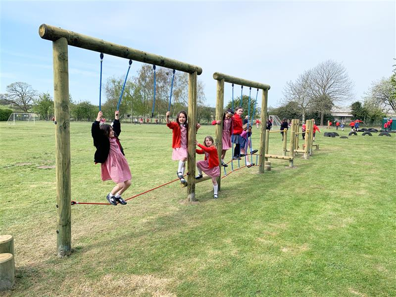 7 children standing on various pieces of trim trail equipment installed into natural grass