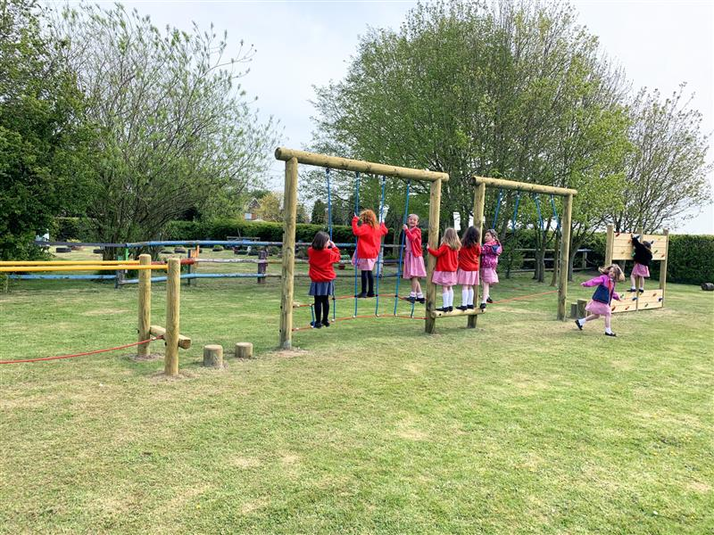 A group of children playing on a playground trim trail