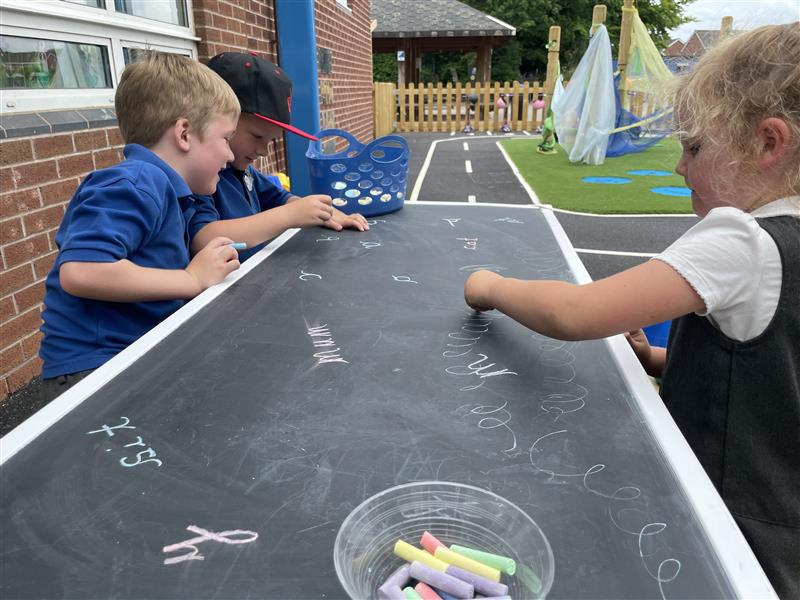 children drawing on our picnic table with chalkboard