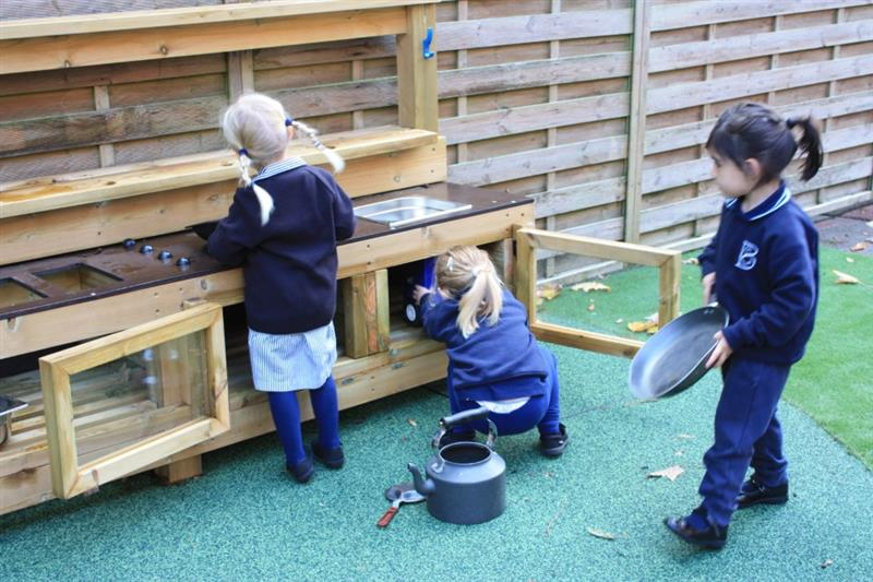 Child putting a mud pie in the oven of a mud kitchen