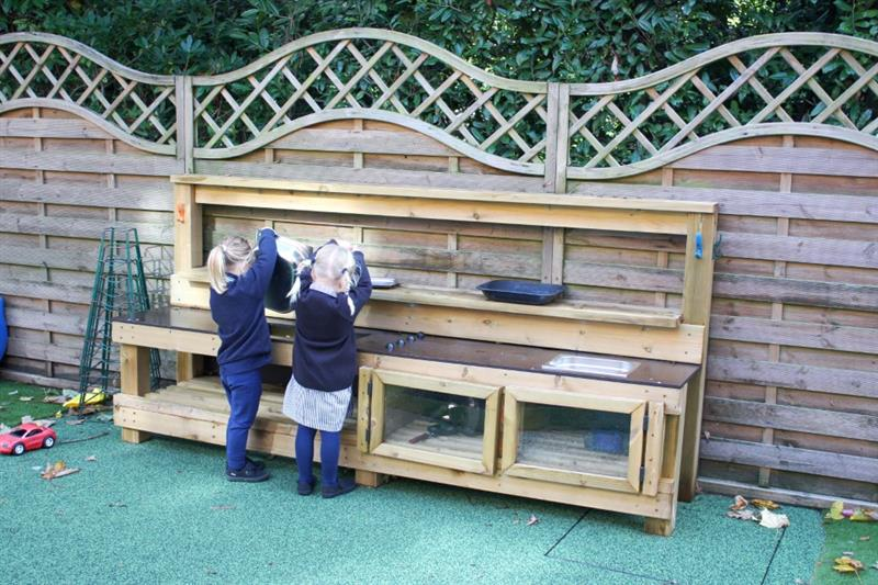 EYFS children playing with a playground mud kitchen