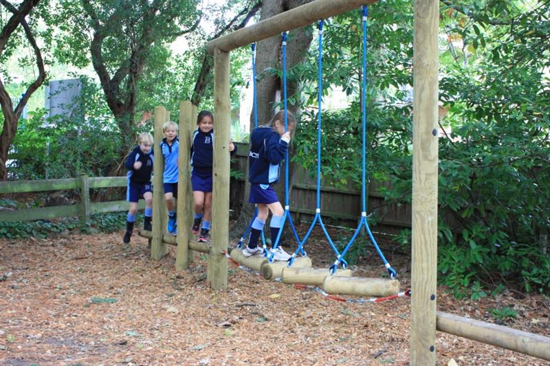 Children playing on school trim trail equipment