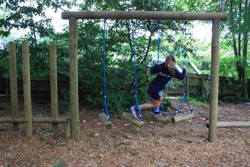 Child swinging on a rope swing traverse on a school playground trim trail