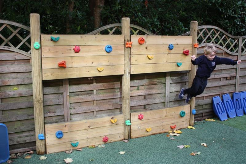 A child jumping off a timber climbing wall in the playground