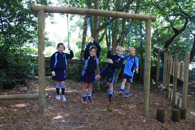 Children standing on timber trim trail equipment smiling
