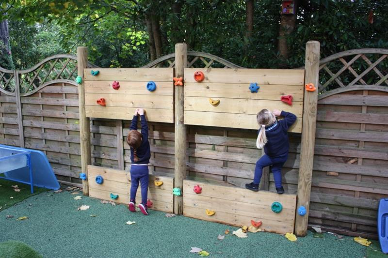 two children climbing on a playground climbing wall