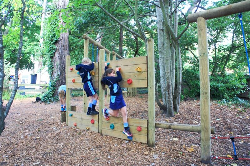 Children moving across a trim trail in the school playground
