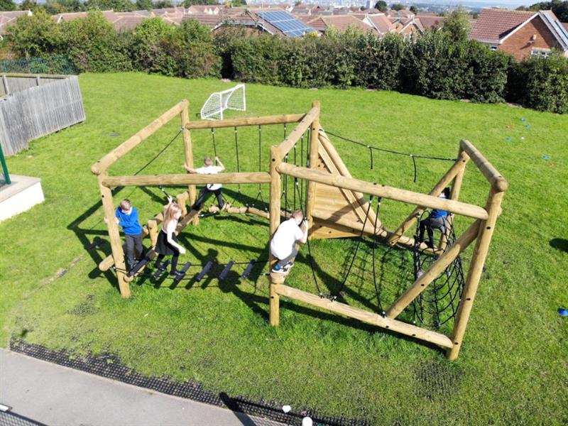 Children playing on a pentagon play climbing frame on their school playground