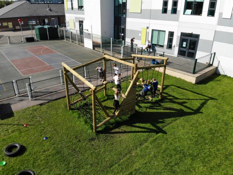 Children swinging on a climbing frame with playground safermats underneath