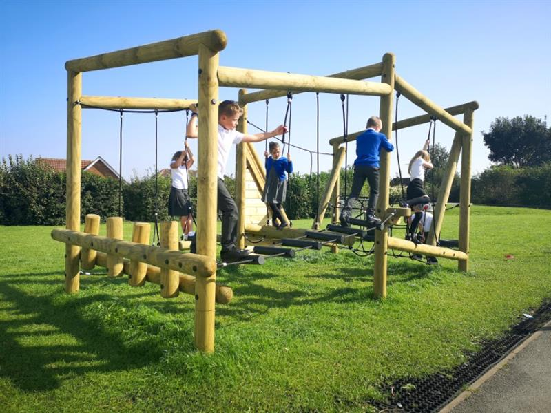Children climbing on a Puzzlewood climbing frame situated on a school field