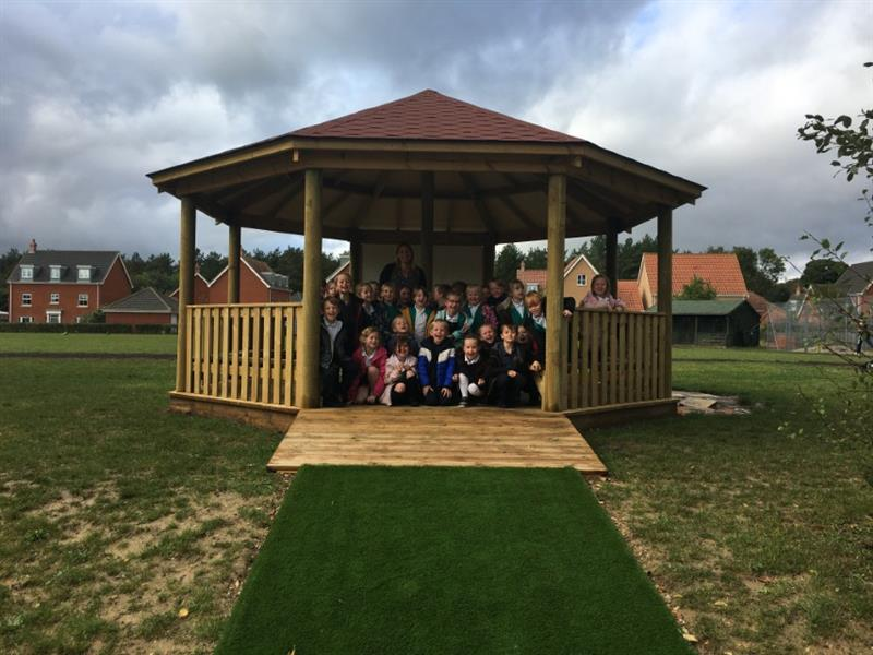Children sat at the entrance of an outdoor gazebo