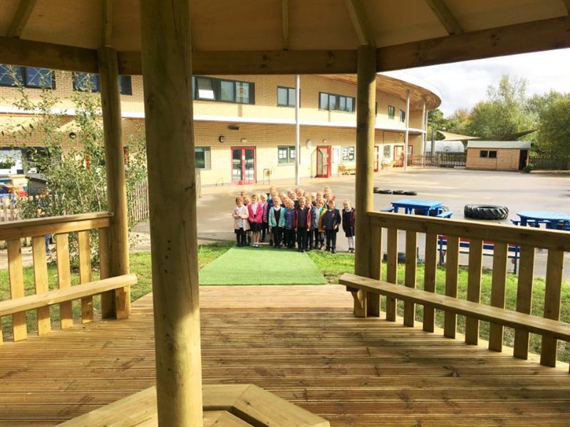 Children stood waiting to enter an outdoor gazebo on their school playground