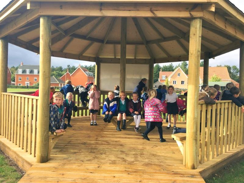 Children playing in an outdoor gazebo on the school playground