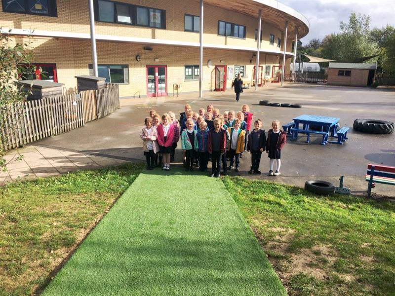 Children stood on artificial grass playground surfacing