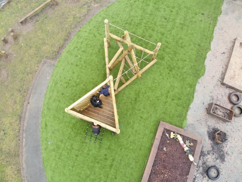 An overhead view of Pentagon Play's Harter Fell Climber with Platform and Climbing Net with a child climbing up the net and 2 stood on the platform