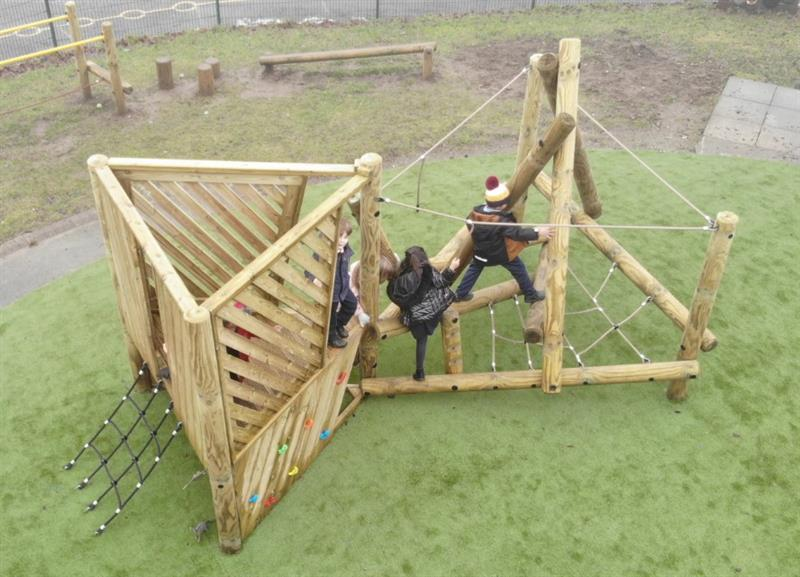 Three children in coats moving across the log climber part of a climbing frame with platform and climbing net
