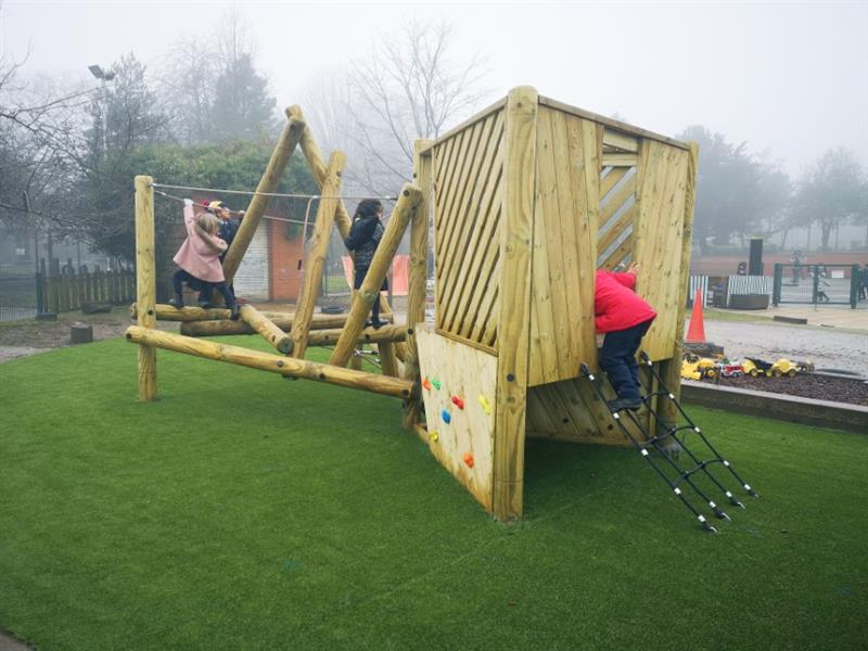 Two children climbing and swinging on the ropes of a log and rope climbing frame and a child climbing up the climbing net onto the climbing frame platform
