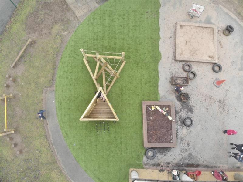 An overhead view of Pentagon Play's Harter Fell Climber with Platform and Climbing Net with 2 children stood on the platform