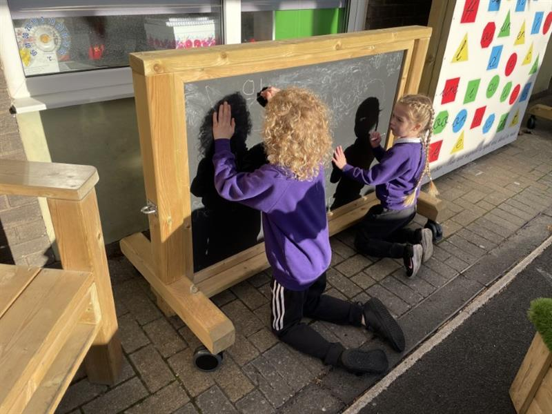 Two children in purple school jumpers kneeling on block paving practicing phonics together on a moveable chalkboard