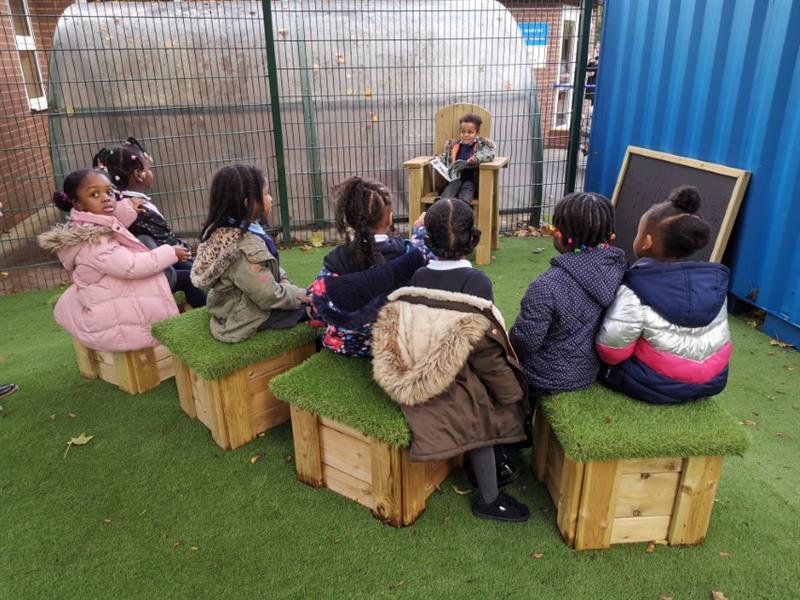 7 children sat in a row on artificial grass topped seats listening to another child read a book sat in a freestanding storytelling chair