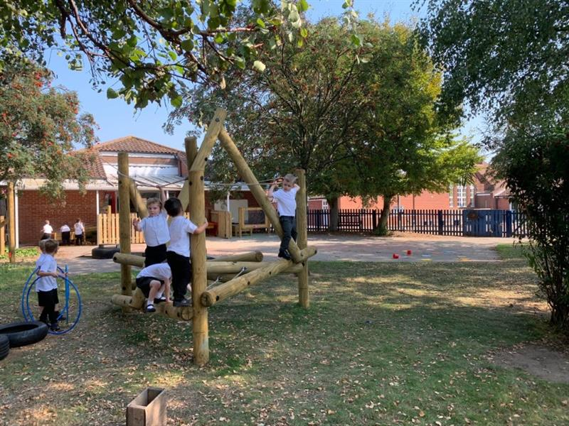 Four children in white polo shirts climbing on Pentagon Plays Harterfell Climbing Frame