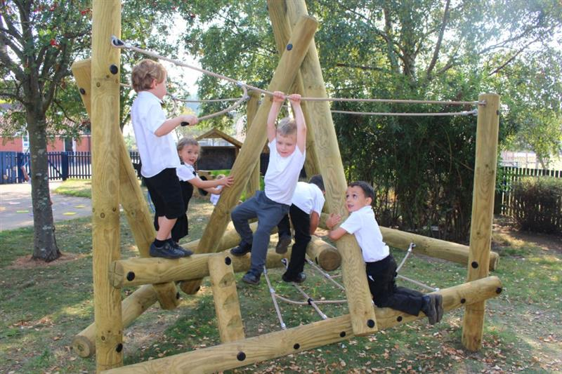 Six children in white polo shirts climbing on Pentagon Plays Harter Fell Climbing Frame