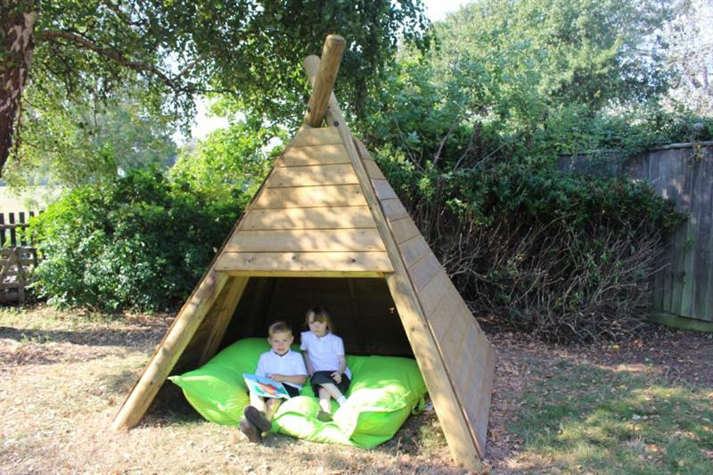 Two children sat underneath a Wigwam Den on a green cushion reading a storybook