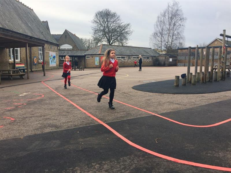Two children in red school jumpers running their daily mile using red line playground markings as a route