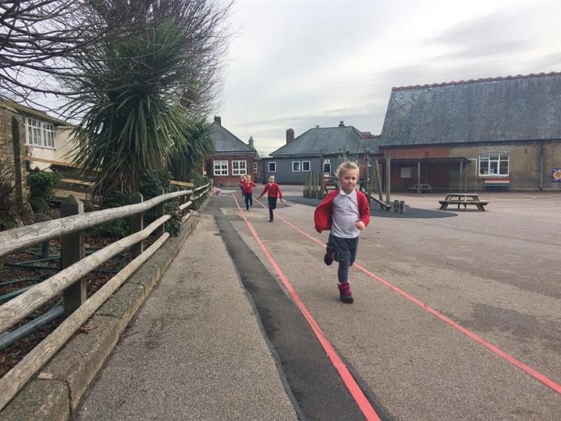 Five children in red school jumpers running their daily mile using red line playground markings as a route