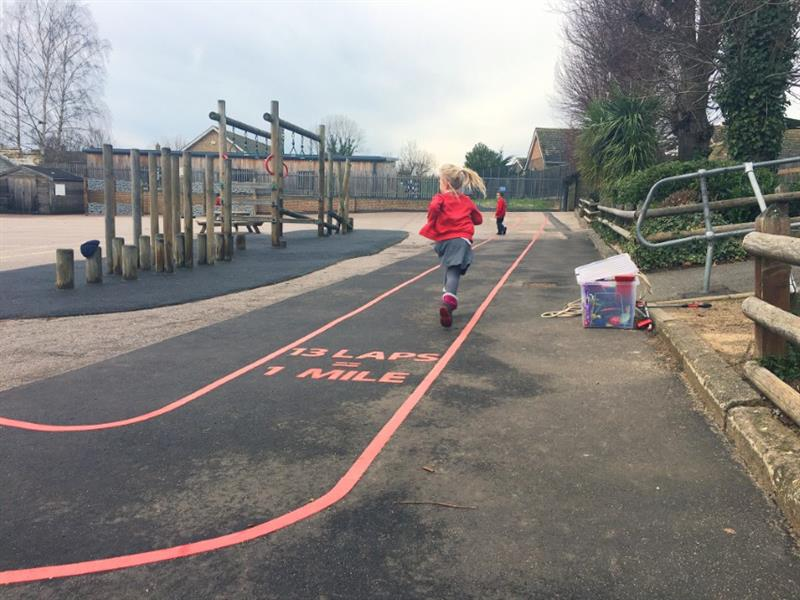 Two children in red school jumpers running their daily mile using red line playground markings as a route with the words 13 laps equals 1 mile in the center of the track