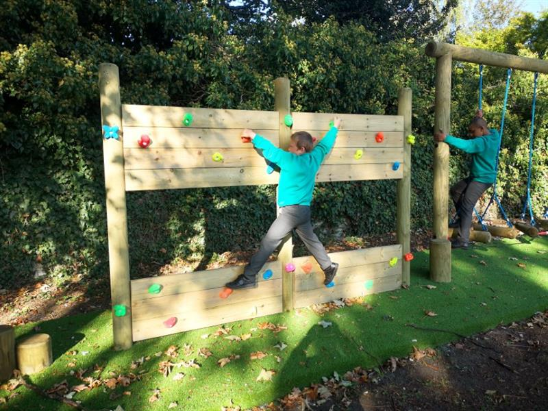 Child climbing across a climbing wall which is part of the new trim trail