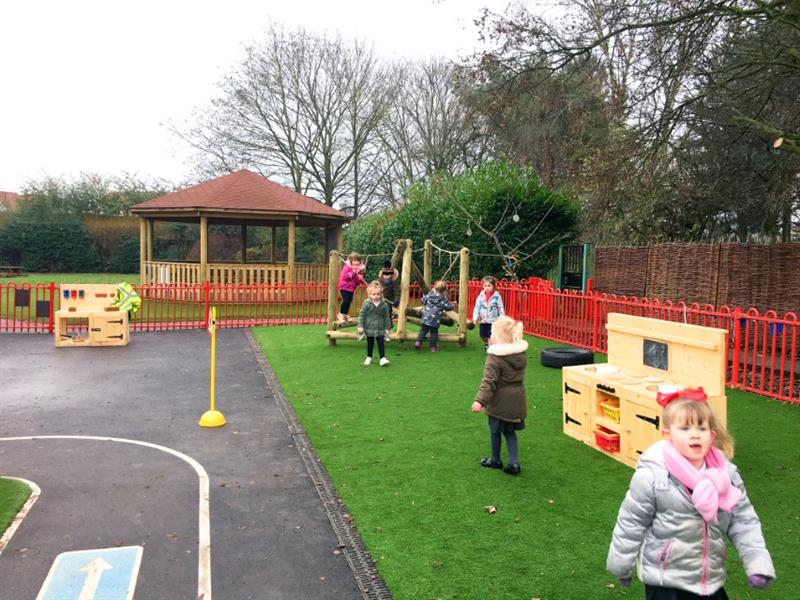 Nursery children playing on artificial grass surfacing