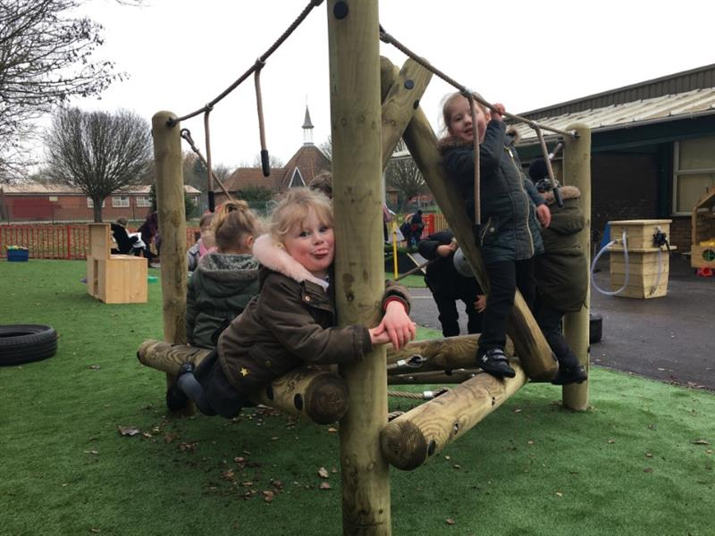 Nursery children climbing on a nursery climbing frame