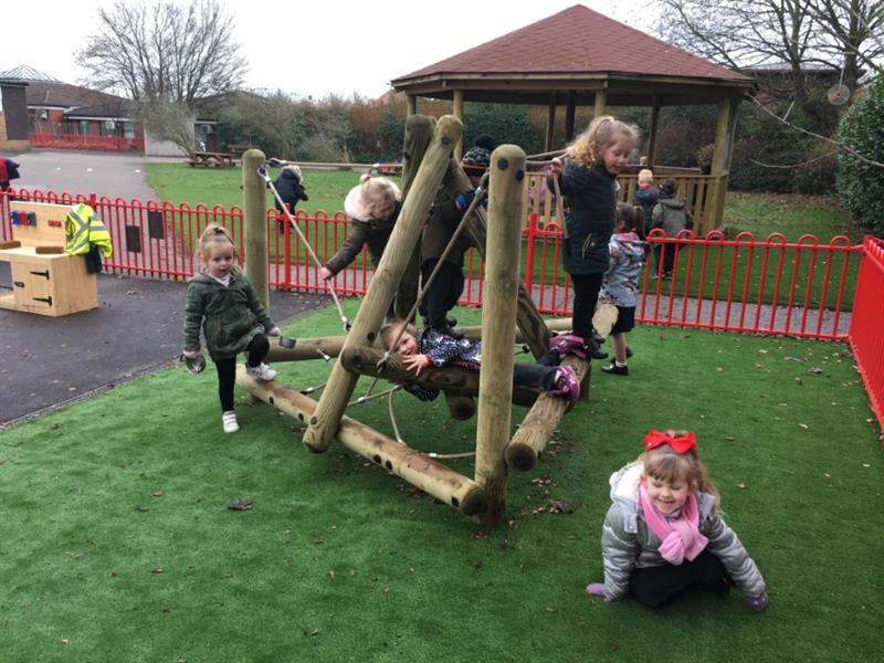 Nursery children swinging and climbing on a nursery climbing frame