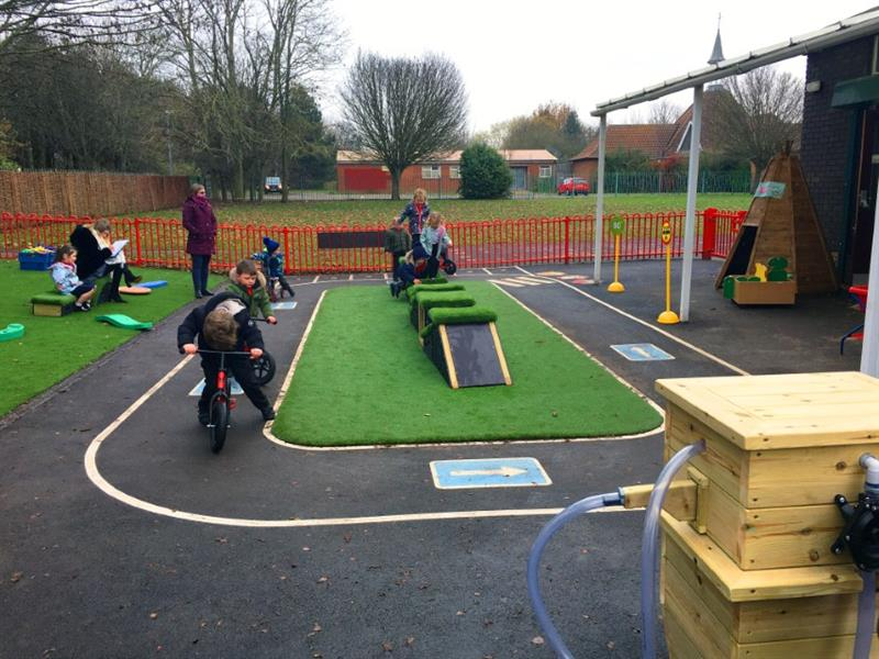 Nursery children racing trikes around the outdoor area