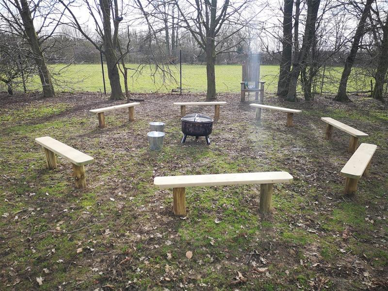Seven perch benches congregated in a circle form with a fire pit in the middle of it. Trees are lined up behind the benches.